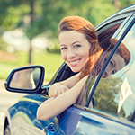 Woman smiling out of her car window